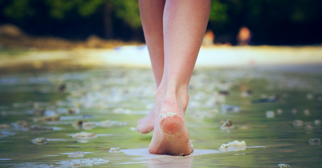 woman walking barefoot water